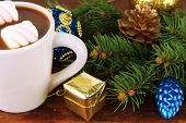 Cup of hot cacao with Christmas decorations on wooden background