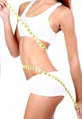 pic of flat stomach  - Beautiful young woman measuring her body with tape isolated on white - JPG