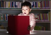 stock photo of shock awe  - Boy surprised by glowing book - JPG