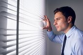 stock photo of blind man  - Side view of a young businessman peeking through blinds in office - JPG