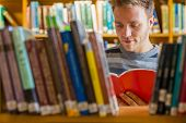 stock photo of homework  - Young male student reading a book amid bookshelves in the college library - JPG