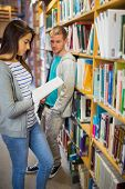 stock photo of she-male  - Blurred young male looking at female as she reads a book against bookshelf in the library - JPG