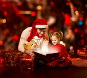 Christmas Family Reading Book. Father And Child Opening Magic Fairy Tale