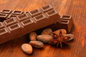 Delicious chocolate bars with cocoa beans close up