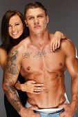 image of striptease  - Young woman embracing man with naked muscular torso - JPG