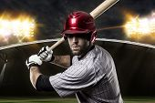 stock photo of ball cap  - Baseball Player on a red uniform on a baseball Stadium - JPG