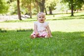 Full length of a happy cute baby sitting on grass at the park