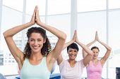 Portrait of sporty young women with joined hands over head at fitness studio