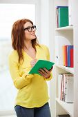 education concept - smiling redhead female student in eyeglasses with textbook in library