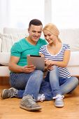 love, family, technology, internet and happiness concept - smiling happy couple witl tablet pc compu