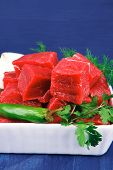 slices of raw fresh beef meat fillet in a white bowls with dill and green peppers serving over blue
