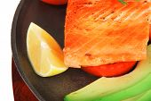 healthy lunch : sea roast salmon on metal pan over red wooden plate with vegetables isolated over wh