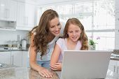 Happy mother and daughter using laptop in the kitchen at home
