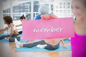 Fit blonde holding card saying member against yoga class in gym