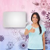 Happy brunette with speech bubble giving thumbs up against digitally generated girly floral design