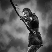 stock photo of archery  - Beautiful archery woman aiming sky on background black and white image - JPG