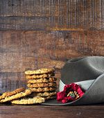 pic of army  - Australian army slouch hat and traditional Anzac biscuits on dark recycled wood with remembrance red poppy for Anzac Day or Remembrance Armistice Day - JPG