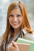 Smiling university student holding books in front of wet window
