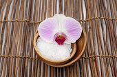 gorgeous orchid with white salt on bowl on bamboo mat