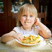 Cute little girl eating Fusilli