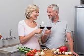 Happy mature couple toasting wine glasses while preparing food in the kitchen at home