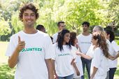 Confident male volunteer showing thumbs up with friends disucssing in background
