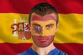 Composite image of serious young spain fan with facepaint against digitally generated spanish nation