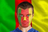 Composite image of serious young cameroon fan with facepaint against digitally generated cameroon na