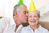 Senior couple sitting on couch wearing party hats at home in living room