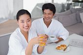 Couple in bathrobes spending the morning together at home in the living room