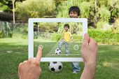 Hand holding tablet pc showing little boy playing football in the park