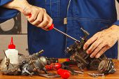 pic of carburetor  - Repairman repairing parts of the old automotive engine in the workshop