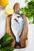 fresh dorado fish and vegetables on wooden board - food and drink