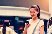 stock photo of ponytail  - beautiful young asian woman using smart phone on shopping street - JPG