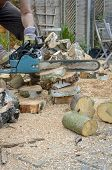 foto of man chainsaw  - Man sawing logs with a chainsaw in his back yard
