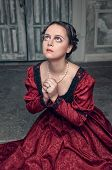 foto of pompous  - Young beautiful medieval woman in long red dress praying in the old room - JPG