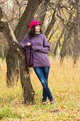 stock photo of knitted cap  - Young stylish woman dressed in oversized knitted sweater skinny jeans peaked cap with big bag in city park - JPG