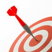 stock photo of bullseye  - Meet target concept using dart pinned at the bullseye - JPG