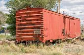 image of boxcar  - Railroad boxcar with a bit of rust parked behind some homes - JPG