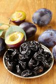 stock photo of prunes  - Dried plums prunes and fresh berries on the wooden table - JPG