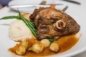 picture of lamb shanks  - A veal or lamb shank on a plate with gravy mashed potatoes green beans and baby onions - JPG