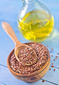 stock photo of flax seed oil  - flax seed in bowl and on a table - JPG