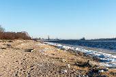 pic of shipyard  - frozen beach near shipyard and sea port with rays of sun and wavebreaker - JPG