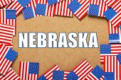 image of nebraska  - Miniature flags of the United States of America form a border on brown card around the name of the state of Nebraska - JPG