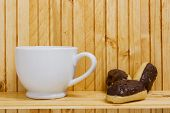 foto of pastarelle  - Mini Eclairs with a cup of tea on the shelf - JPG