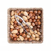 foto of mixed nut  - Mixed nuts in a woven basket with nut cracker isolated on white - JPG