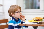 picture of hamburger  - Cute little boy with glasses eating fast food - JPG