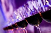 picture of sparkling wine  - Glasses with red wine lit by nightclub lights - JPG