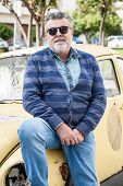 foto of beetle car  - Man with an old classic yellow street wolsvagen beetle - JPG