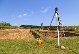 pic of geodesic  - Surveying measuring equipment on tripod at neolithic excavations site on field - JPG